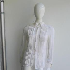 """Varetype: Silkeskjorte med manchetknapper silke skjorte eksklusiv læg bieser biser Størrelse: 2 Farve: Creme Oprindelig købspris: 2800 kr.  Beskrivelse: Super flot gennemsigtig silkeskjorte. Den er brugt et par gange og vasket i hånden. Jeg er for doven til at stryge og derfor sælges den.  Selve skjorten er gennemsigtig i en cremefarvet silke, kraven og manchetterne er i en mere lys/hvid fed silke.  Knapperne er skjult bag en stolpelukning (hvilket ikke ses, da den ikke er strøget). Ned foran er der på begge sider læg / bieser. Den nederste knap går igennem stolpelukningen og er en guldknap.  Man kan naturligvis udskifte de silkeknapper der er ved håndleddene til guldknude manchetknapper, så de matcher knappen. Så flot og eksklusiv.  På ryggen går der hele vejen ned i midten en stribe med stof.   Størrelse: 2 (jeg vil mene den svarer til ca xs/s, nok mere xs end s. 34, xsmall, xtra small, 36, small) Se nedenstående mål.  Mål:  Længde: 65,3 Ærme: 62 Bryst: 45,5 x 2 Nederst: 43 x 2  Materiale: 95% silke, 5% spandex Mærke: Hilfiger Collection, der er en dyr kollektion fra """"hovedmærket"""" Tommy Hilfiger - dvs det er ikke en almindelig Tommy Hilfiger skjorte.  Nypris: 2.800 Vægt: 99 gram  Klik på Køb nu knappen og køb med det samme. Hvis der er mere på min profil du ønsker at købe med, tilføjer du blot det.  Mine annoncer er delt op i kategorier, dvs. alle jeans, jakker, kjoler etc. er samlet hver for sig på profilen. Scrol og se alle ting i shoppen. Dukken er en str xs/s og 174 cm til sammenligning."""