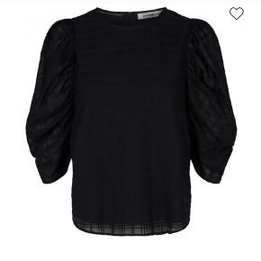 Sød bluse fra Co'Couture i sort med et flot mønster i vævet tern og transparente puf ærmer, som giver et super flot look. Blusen er med rund hals, og en fastsyet underdel.   Almindelig pasform og lukkes med lynlås i nakken.   Str. M måler i længde: 59 cm ( længde fra skulder og ned. Bryst: 106 cm ( omkreds mål )  Materiale: 100 % bomuld