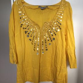 Super fin solgul bluse med palietter i etnisk stil fra Zara. Det er 100% bomuld og den er Made in India. Den er slidset lidt op nederst på ærmet og på kropsdelen. Str. L. Kom med et bud. NP: 350kr.  Varen befinder sig i 9520 Skørping. Sender med DAO.  Se også min øvrige annoncer. Jeg sælger tøj, sko og accessories. Pt er min shop fuld af vintagekup, high street fund og mærkevarer i mange forskellige str. Kig forbi og spøg endelig!
