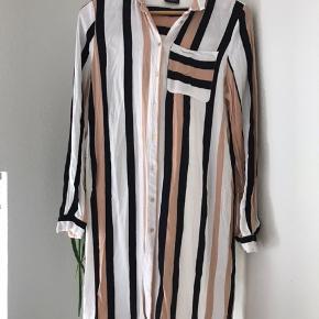 Lang skjorte der kan bruges som cardigan også. Har en brystlomme på ene bryst. Lukkes med knapper.