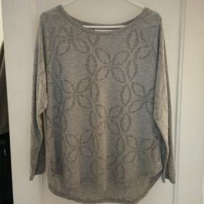 Fin hulmønstret grå bluse med 3/4 lange ærmer og buet kant i bunden. 65% polyester/35% viscose. Brugt 1 gang.  Mål Længde: 65cm Bredde: 57cm