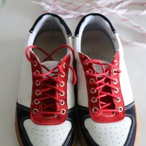 Den sejeste par sneakers fra Mads Nørgaard i blå og rød ruskind, med hvid skind. Jeg har skiftet snørebåndene til røde, men de originale snørebånd følger med.   Brugt med i rigtigt god stand.