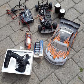 Fjernstyret  bil med 2 sæt batterier og lader og 3 sæt dæk. (2 indendørs og et sæt udendørs dæk)  500 kr