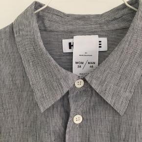 Flot skjorte fra Hope i str 38. Gråmeleret i en skøn kvalitet af 79% bomuld og 21% Lin. Bred model med en stor forlomme. Krave og knaplukning.  Overvinde: 124 cm Længde: 77 cm