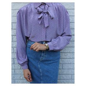 Cute vintage silk shirt💜 Lækker vintage skjorte i silke i en flot pastel lilla. Skjorten har de flotteste blomster motiver, og en sløjfe som giver et ekstra pift. Passer både til hverdag og festlige anledninger. Fits: 34-40.
