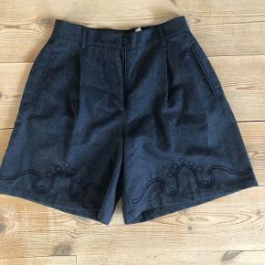 Flotte højtaljet shorts med bredde ben.   De er købt vintage, men fremstår uden brugsspor - de er i vældig flot stand.   Shortsene har to lommer og lukkes med en lynlås og knap. Foran, forneden er der broderet et fint mønster.   Mål Længde: ca. 49 cm.  Bredde (taljen): ca. 37 cm.   Jeg vil sige, at de passer en str. 32-36   Shortsene er lavet af 100% Lana wool