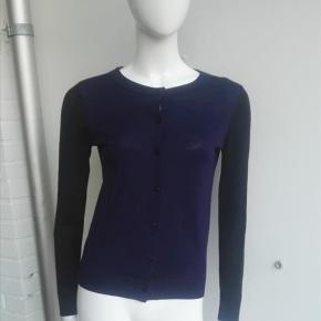 Varetype: Cardigan i 100% merinould tofarvet merino uld, strikcardigan strikbluse bluse trøje strik Farve: Mørkeblå, sort, navy, blå Estimeret nypris: 999 kr.  Beskrivelse: Super lækker tynd cardigan i to farver. Jeg har brugt den under et jakkesæt. Den er mørkeblå foran og en kant rundt i kraven, ellers er den sort på ærmer og bagpå. I siden mellem for og bag går den en lille smule ned, så den er lidt længere bagpå end foran.  Der er en lille bitte smule fnulder under armene. Den sælges kun fordi jeg ikker har lukket munden og er blevet for tyk.   Størrelse: S (small, 36 - jeg synes den svarer mere til en xs, xtra small, 34 xsmall. Dukken er en xs/xs. Der er mål af dukken på min første annonce (FAQ). Eller se nedenstående mål og sammenlign.  Mål:  Længde: 57 cm / 58,2 Ærmemål (målt fra skulder ned): 61 cm Bredde lige under ærmegab (hen over brystet): 43 x 2 cm Længden under armen og ned (der hvor ærmet er hæftet på):38,5 cm til den blå side Bredde forneden: 35  x 2 cm  Materiale: 100% merinould Mærke: & other stories, And other stories Vægt: 163 gram  Klik på Køb nu knappen og køb med det samme. Hvis der er mere på min profil du ønsker at købe med, tilføjer du blot det.  Mine annoncer er delt op i kategorier, dvs. alle jeans, jakker, kjoler etc. er samlet hver for sig på profilen. Scrol og se alle ting i shoppen. Dukken er en str xs/s og 174 cm til sammenligning.