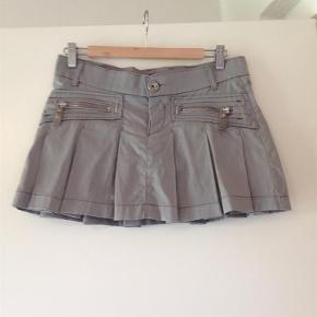 Varetype: nederdel Farve: Grå Oprindelig købspris: 999 kr.  Fed kort nederdel fra Miss Sixty - lavtaljet. Nederdelen er i lidt blankt stof i farven sølv/grå. Der er elastan i stoffet og den kan derfor godt passes af en str. M. Kom med et bud.    Bytter ikke.
