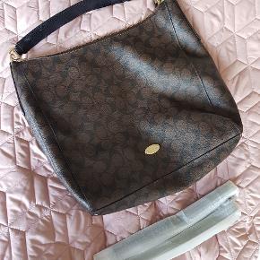 Lækker brun Coach taske som næsten ikke er brugt. Den har et stort lækkert rum med plads til en del. Der hører en skulderrem til som heller aldrig er brugt.