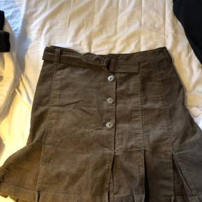 Rigtig sød og unik nederdel i fløjet. Nederdel har lidt ekstra foldet stof ned for neden, knapper og et bælte i taljen🌸