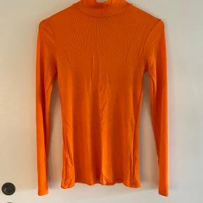 Turtleneck i orange ribstrik fra & Other Stories. Lækkert og glat materiale. Str 34.