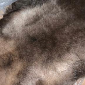 Rensdyrskind tæppe.  Skal lægges et fredeligt sted, da hårene ellers kan knække og fælde, hvis man går eller sidder på skindet.  Oprindelsesland: Finland.