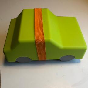 Toplækker madkasse i robust plast til det bilglade barn. Fra Invotis by Chris Koens. Limegrøn med orange elastik. Måler 12,9x11,2x20,3 - så god plads til mad og snacks. Kan gå i opvaskemaskinen, Ingen skader. Fra røgfrit hjem