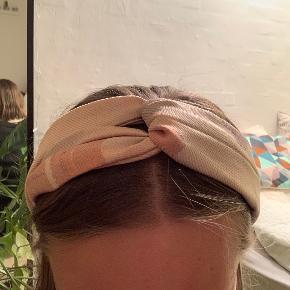 Emmahårbåndet med den klassiske snoet detalje, og elastik i nakken.  Hårbåndet er lavet af genbrugsmaterialer og passer alle størrelse hoveder.