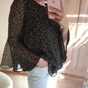 Fin og let bluse fra Y.A.S.  Blusen har store ærmer og en løs pasform. Blusen er dekoreret med små gule og violette blomster. Brugt en gang, så den er i rigtig flot stand.  Blusen lukkes med en enkel knap bagerst.