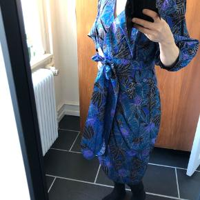 Den smukkeste vintage kjole i thai silke. Der er slå-om-effekt med knapper og et bælte til, hvis man vil have endnu mere talje fremhævet. Størrelsen er et bud, da der ikke er mærke i. En M/L vil passe en fint.