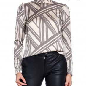 Flot bluse med grafisk print fra Neo Noir. Blusen er råhvid med grå print. Blusen har høj hals som knappes i nakken. Læg på skuldrene, og knapper med manchet. Kvalitet: 100% polyester. Passes også af str. L.  Se også mine andre annoncer 🌸🌸