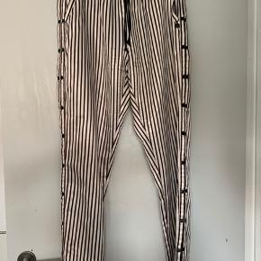 Super lækre bukser i polyester med pynteknapper langs siden. Brugt og vasket 5 gange. Str. 2 svarer til en small/medium.