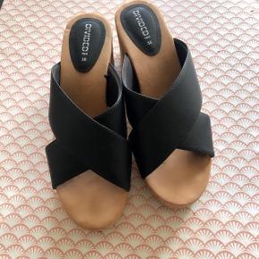 Divided sorte høje sandaler str 38 . Hælen er korklignende og måler i højden 7 cm.