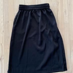 Sort og hvid midi nederdel fra Monki med elastik i taljen. Str. XS, men passer fint en S.   Afhentes på Frederiksberg eller sendes for købers regning.