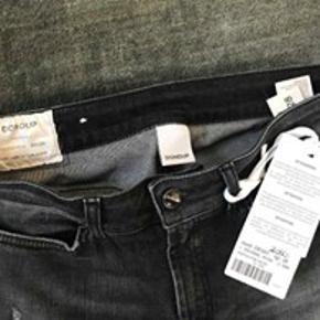 HELT NYE, Super seje Dunlop flared jeans str. 28. Aldrig brugt, med tag.  Flot sortblå farve. stretch, rå kanter forneden. Nypris 2000.-  Kan ses i Rungsted. Sender gerne