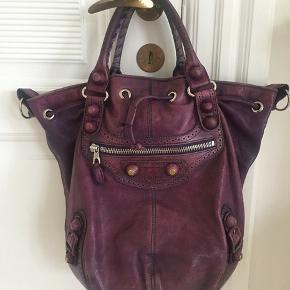 Sælger denne skønne Balanciaga Pom Pom taske i det kraftige skind med store læderbetrukne nitter, har masser charme og patina og mange godt år i sig endnu.