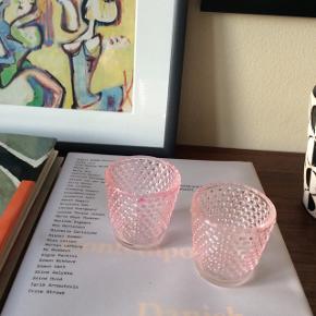 2 lyserøde fyrfadslysstager i glas. Ca. 6x6 cm.  20 kr. for begge. Fast pris.  Mødes og handle på Nørrebro i området: Runddelen, Jægersborggade og Stefansgade. - Sender ikke.  Bytter ikke.