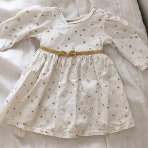 """2 fine baby kjoler med """"indbygget"""" body i begge.  Den ene er hvid med tyl og sløjfe  Den anden er hvid med guld stjerne og sløjfe - og har lidt tyl også.   Røgfrit Dyrefrit"""