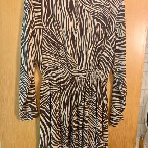 Super sød og luftig sommerkjole med brune zebra-agtige striber. Lukning med knap i nakken og lille nøglehulskig til hud øverst på ryggen. Lange ærmer, elastik i taljen og super fin pasform. Aldrig brugt! 😍