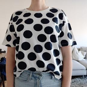 White shirt with navy blue polka dots. The fit is lose and slightly cropped in length.