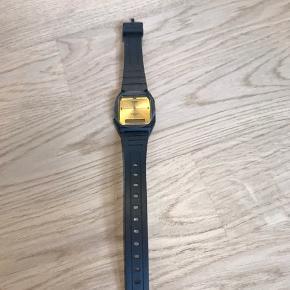 1 flot Casio armbåndsur med sort rem og guldfarvet display. Aldrig brugt, så stadig beskyttelses-plastik på display.