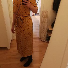 Fin kjole med bindebånd og trykknapper som lukkemekanisme. Kjolen kan også bruges åbenstående som kimono.