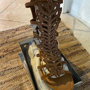 Nok sommerens fedeste sandal. Total skinnende. Får masser af opmærksomhed. Sandalen er blød og med super lækker komfort. Farven er camel Nye og ubrugte.