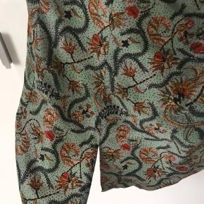 Fineste en armede top i 100% silke. Den lukkes med en lynlås på ryggen. Toppen er tætsiddende om livet dig og bliver meget løser for oven (Ved barmen). Trøjen passer bedst en faktisk 38 - da det er silke som ikke ændre sig meget når man har den på.