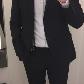 Sælger dette jakkesæt købt i december. Det er brugt én enkelt gang, da jeg desværre har været for optimistisk med størrelsen. Kan prøves i Vanløse.  Obs. farven er sort, sidste billede er af samme model for at præsenteret hvordan jakkesættet sidder