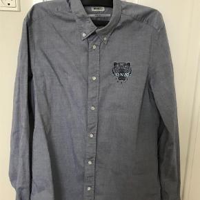Varetype: Skjorte Farve: Blå  Lækker herreskjorte i oxford stil med bottondown. Mellemblå farve.   På manchetten er der en knap som er knækket(halvdelen sidder fortsat på - se billede) pris sat derefter. Det påvirker ikke brugen men kan udskiftes med en alm skjorteknap.   Str 39/ 15 1/4 men svarer til en str s