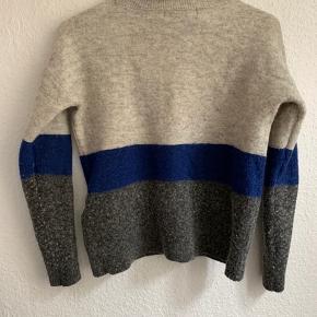 Lækker uldstrik fra Vero Moda med høj hals. Lidt lille i størrelsen men holder formen. Dejlig varm til efterår og vinter.