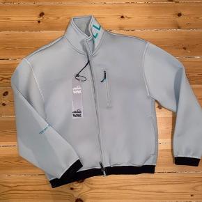 Wood Wood X Ellesse COLAB. Tech stof, trøje. Flot meget lys blå med turkise detaljer (se billeder). Aldrig brugt og fremstår perfekt (med tags). Køber betaler selv for forsendelse - kan mødes og handle i Storkøbenhavn for at undgå fragt :)