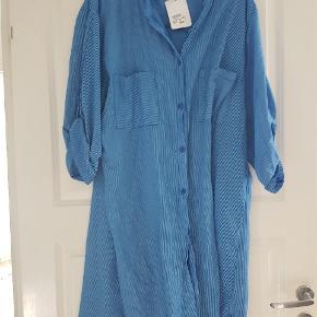Skjortekjole i bomuld med knapper og brystlomme. Købt i Nanna xl, og aldrig brugt. Pris fra ny 300 kr. Længde 102 cm Brystmål 122 cm