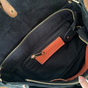 Fed taske i ruskind. Den er næsten ikke brugt, men eftersom den er i ruskind så bliver det hurtigt lidt nulret