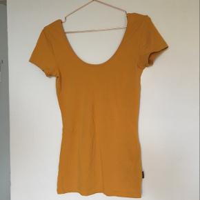 Mustardy-orange t-shirt with a deep/low neck and back. Tight fit and long.