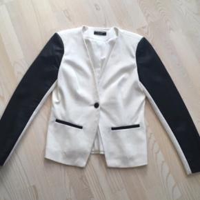 """Perfekt til efteråret.  Skøn hvid blazer fra Vila. I sweat stof med PU læder ærmer og sort knap. God men brugt, eneste """"slid"""" er at bagpå ærmer på det hvide er den lidt nusset. Nypris 400,- pris 65,- afhentet i Ikast eller plus porto (38 med DAO).  Se også mine andre fine og billige annoncer - giver gerne mængderabat :)"""