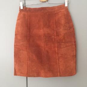 Smuk vintage ruskinds nederdel som passer en str S/M. Sidder rigtig flot på! Har dog lidt tegn på slid og har en enkelt revne bagpå som er syet sammen