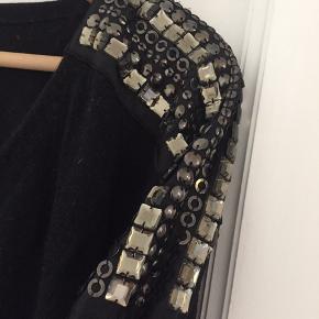 Sort strik med v-hals og perler på skuldrene. Enkelte af perlerne er faldet af. Billede i kommentar.