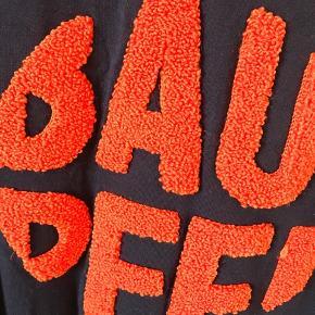 Fed T-shirt i navyblå med orange skrift. Brugt få gange. Står som ny.