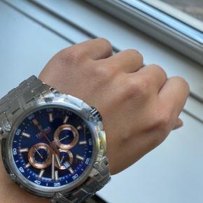 Lækkert tidløst ur med flot blå skive. Det er muligt at skifte remmen ud med en mindre prangende denimblå rem. Uret er aldrig brugt, så det fejler absolut intet, leveres i original æske og er forsat med film på glasset.   Kom gerne med et bud realistisk bud
