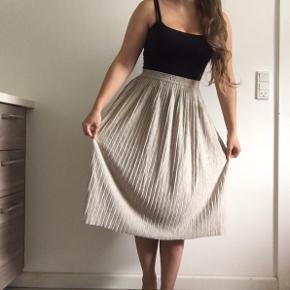 """Fed plisseret midinederdel. Nederdelen er gråbeige og fnulrer lidt. Der er elastik i livet. Har klippet mærket ud, men der står """"made in Denmark"""" indeni.   Søgeord: midi"""