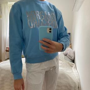 Lyseblå sweatshirt fra Mads Nørregaard. Brugt Max 2 gange, nærmest som ny.  Str. 14 år. Svarer til en xs da fittet er løst. Jeg er 165 høj og bruger selv xs/s i overdele.   Skriv gerne for flere billeder
