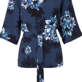 Varetype: Smuk printet bluse Farve: Blå Oprindelig købspris: 600 kr.  Elegant bluse med smukt blomsterprint fra mbyM.    Blusen har bindebånd i taljen, som kan bruges til at fremhæve taljen, men blusen kan også bruges løs. Blusen har korte ærmer og rund halsudskæring.    Kvalitet: 100% viskose    Som ny brugt få gange.