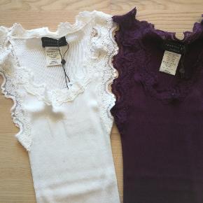 To Dejlige Rosemunde Toppe - ubrugt.  Materiale: Silke + Bomuld  Større: M  Farve: blomme + hvid  Nypris: 600,- Sælges for 239,- (+ porto) Total for begge.